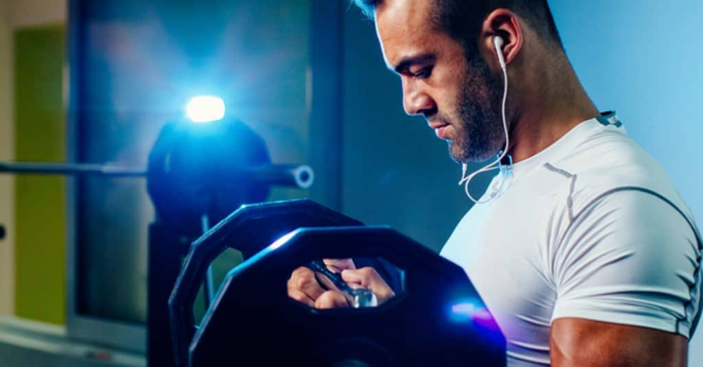 Man lifting weights with ear buds in.