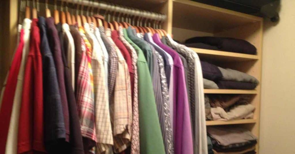 Organized clothes in a small closet.