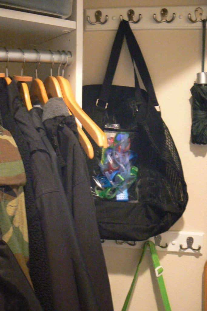 Swim bag and umbrella handing in the coat closet.
