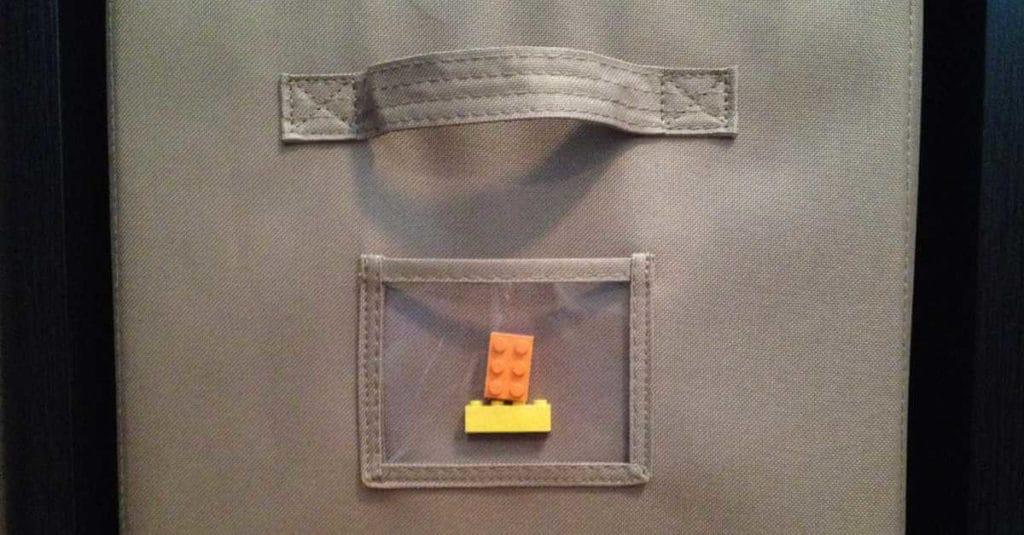 LEGOS organized in fabric drawers on a bookshelf.