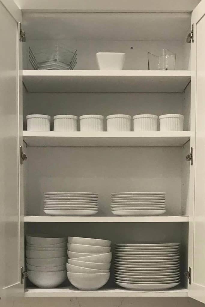 White dishes organized in a cupboard.