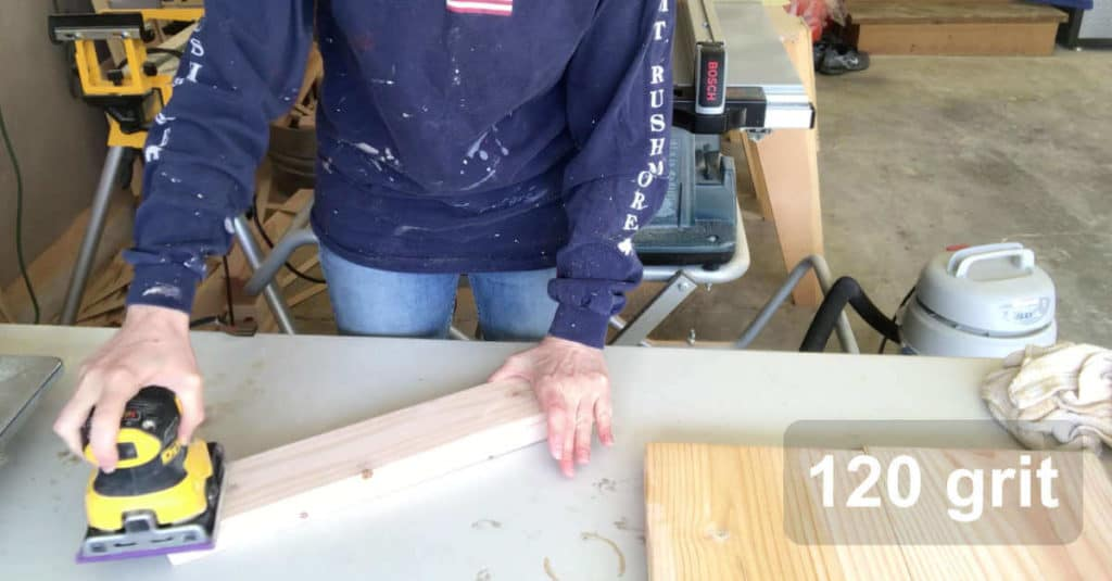 Sanding a small bench leg with 120 grit sandpaper.