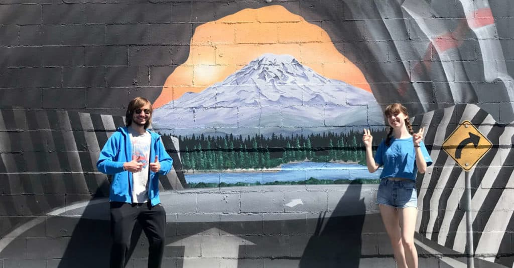 Teenagers taking photos in front of a mural painted on a building.